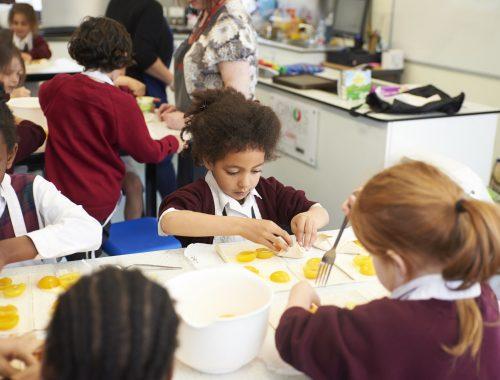 school children making pasta